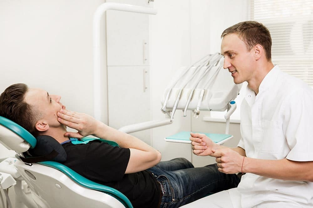 Guy holding cheek in dental chair with dentist