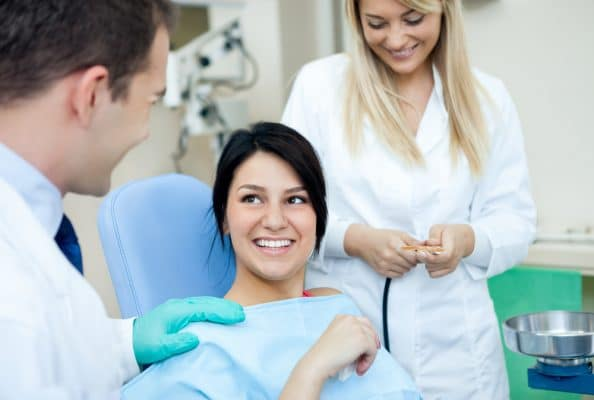 woman sitting in dental chair smiling as the dentist smiles at her