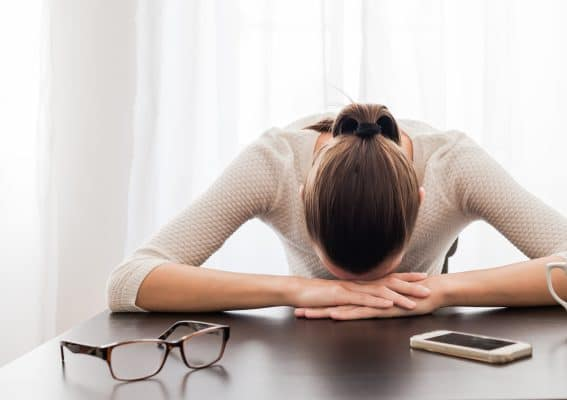 Woman resting head on desk due to fatigue