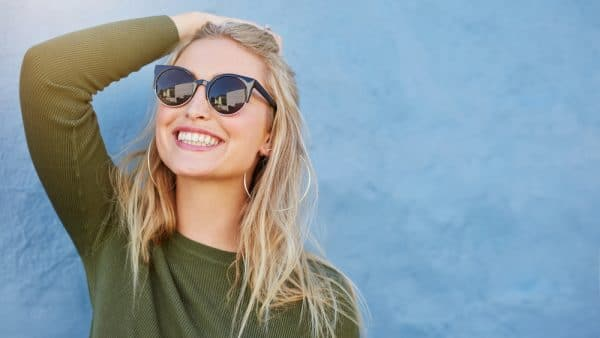 blonde woman standing in front a blue wall and smiling with sunglasses on