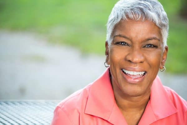 older black woman with short grey hair wearing a pink blouse and smiling